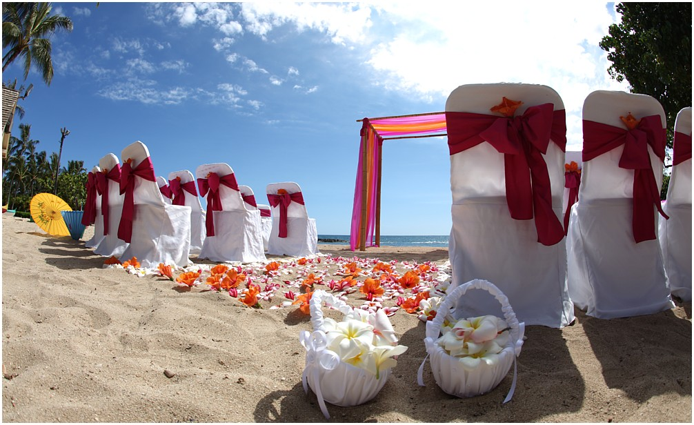 Hawaii beach wedding with dark pink sashes for the chairs with flowers form Hawaii