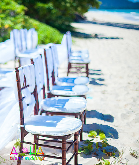 dark wood chairs on the beach with white material