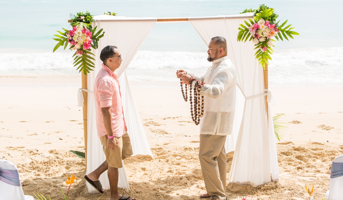 arch in Hawaii with groom giving flower lei