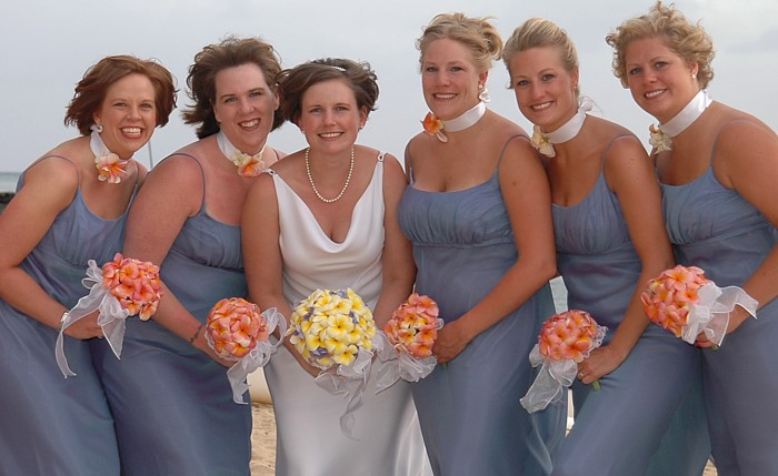 bride and bridesmaids hold plumerias of pink and yellow