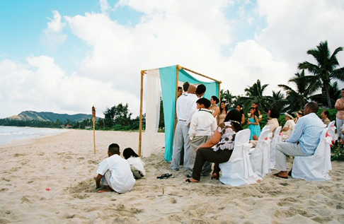 Arch on the sand with kids playing during the ceremony
