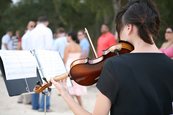 violinist playing at a wedding in Hawaii reading her music