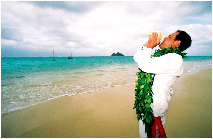 the groom blowing the conch shell for his bride