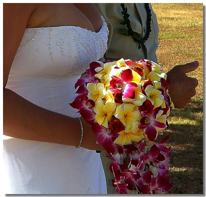bride holds purple orchid and yellow plumeria bouquet