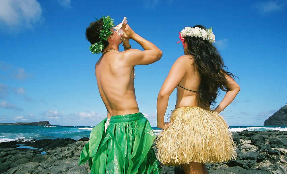 groom in traditional Hawaiian hula skirt blowing the conch shell conch