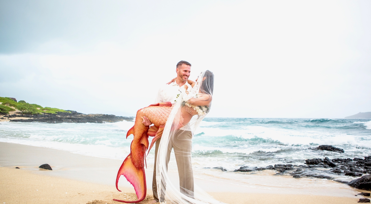 Holding his mermaid on the beach after their wedding ceremony